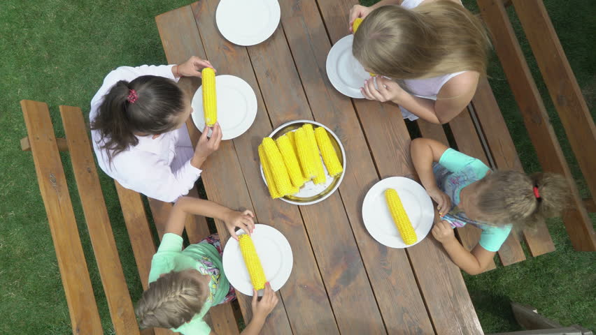 Family corn eating contest in the garden. Children have fun eats sweet corn cob at a wooden table outside. Top view of eaters on green grass lawn. High angle jib crane shot. | Shutterstock HD Video #29803354