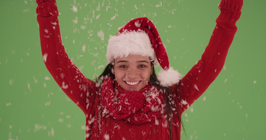 Happy Latina girl in a Christmas hat on green screen. On green screen to be keyed or composited.
