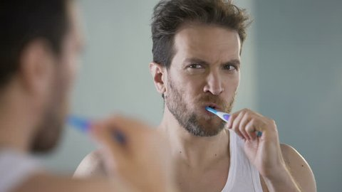Middle-aged bachelor brushing his teeth, morning routine, taking care of health