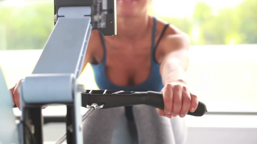 Woman training on a rowing machine in gym