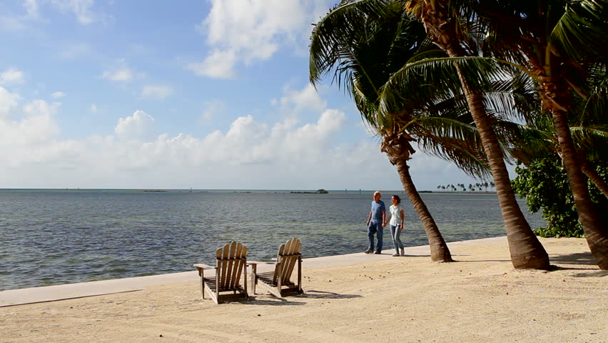 Retired husband and wife hold hands and stroll along the coastline at a resort in the Florida Keys.