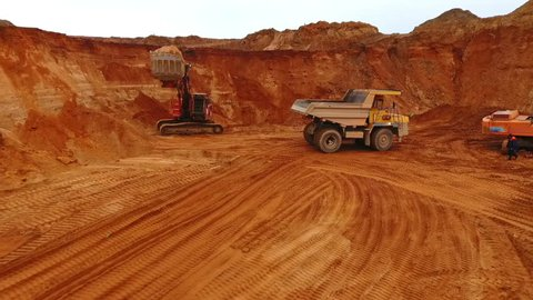 Mining machinery working at sand quarry. Dumper truck working at sand quarry. Industrial machinery of mining industry