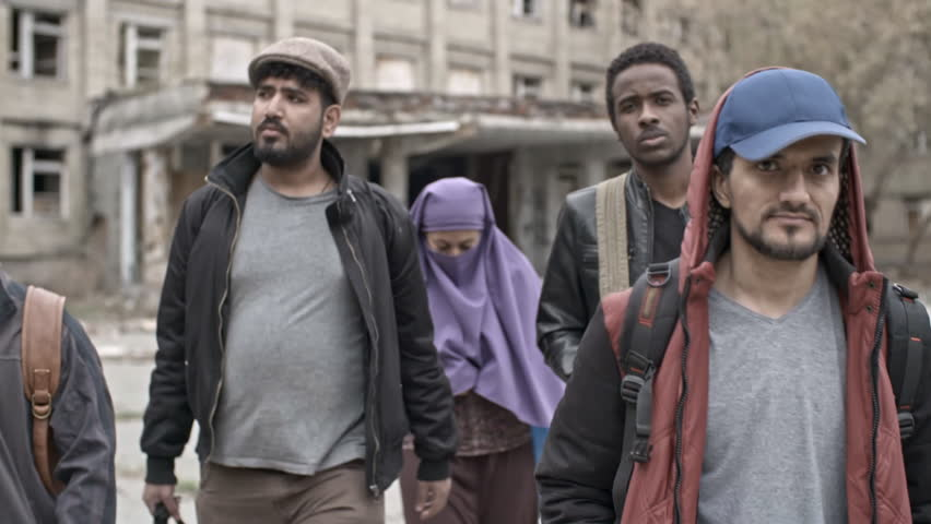 Dolly of group of serious male Arab refugees and Muslim woman in purple niqab walking towards camera; soldiers in uniforms patrolling before abandoned building in background