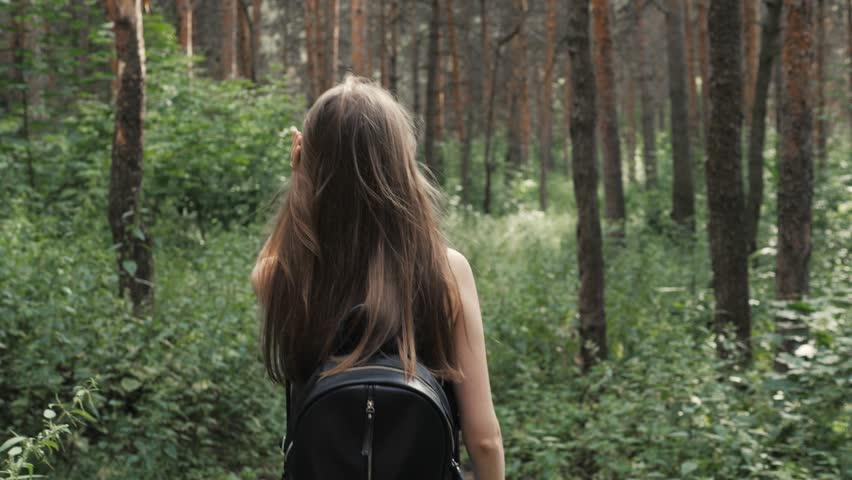 On a sunny day, a portrait of a beautiful young tourist girl, with a backpack, fashion woman, walks through the forest, the background of trees. Concept: recreation, beautiful view, sports, travel.