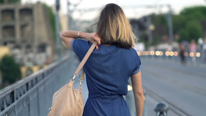 Young woman walking near street in city, super slow motion 240fps