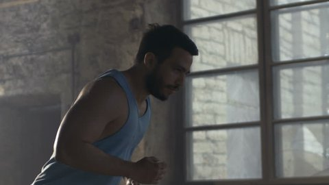 Muscular Man in Sleeveless Shirt Runs in Abandoned Industrial Building. Shot on RED EPIC-W 8K Helium Cinema Camera.