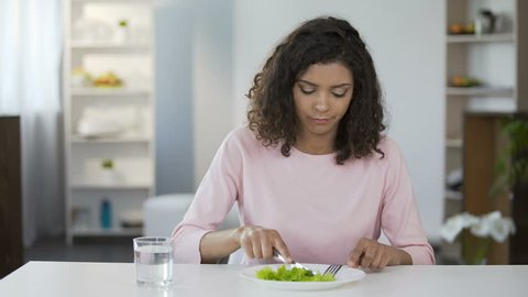 Young woman forcing herself to eat salad, dissatisfaction, weight control, diet