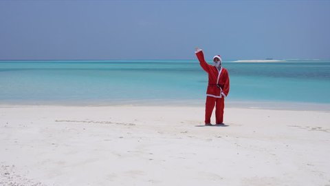 Man in Santa Claus costume on sandy tropical beach. Christmas and New Year celebration on Maldive island