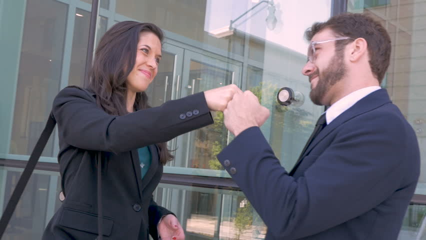 A happy millennial businessman and businesswoman celebrating with an exploding fist bump outside a modern glass office building in slow motion | Shutterstock HD Video #29994694