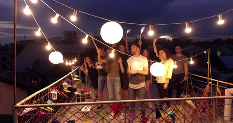 Aerial Flight Around Diverse Young Party Friends On Rooftop Cheerful Partying Shooting Fireworks New Years Eve Party Festive Time Happy Event Concept At Night