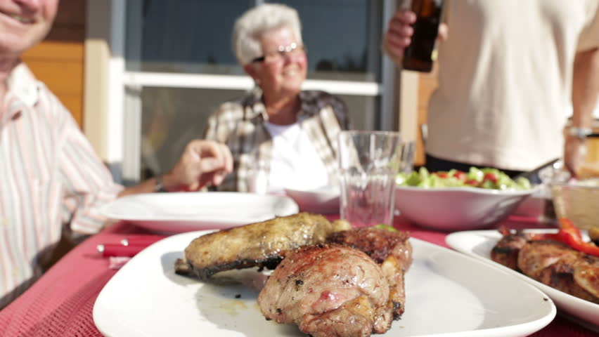 dolly shot seniors at barbecue table with beer outdoors on terrace