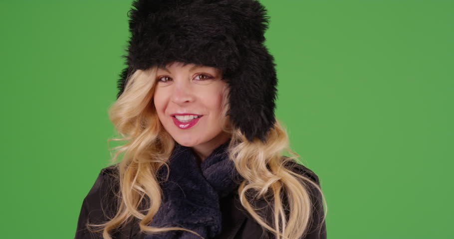 Close up of cheerful Caucasian woman in fur cap and scarf smiling at camera outdoors in snow on green screen. On green screen to be keyed or composited.