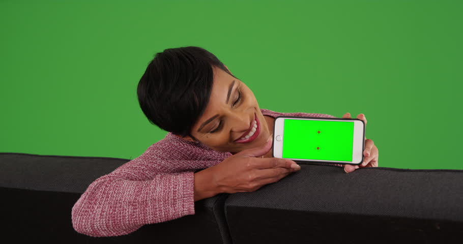 Portrait of smiling black female sitting on couch holding smart phone with green screen on green screen. On green screen to be keyed or composited.