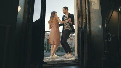 Sexy couple dancing at a party on balcony slow motion. Man and woman dancing at on a summer day on background european city. Happy couple having fun at a party on a sunny evening full length view