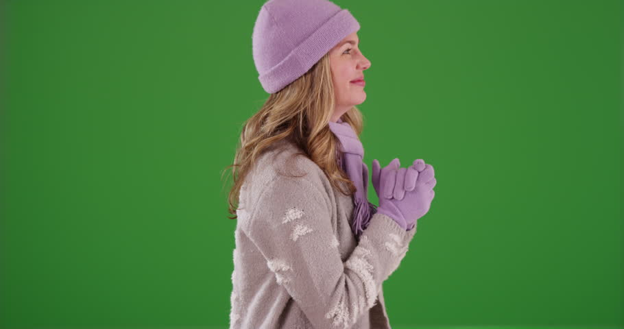 Profile of middle aged Caucasian woman in the snow on green screen. On green screen to be keyed or composited.