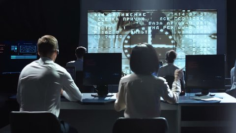 Back view of people working and managing flight in mission control center. Docking to the international space station in space then celebrate.