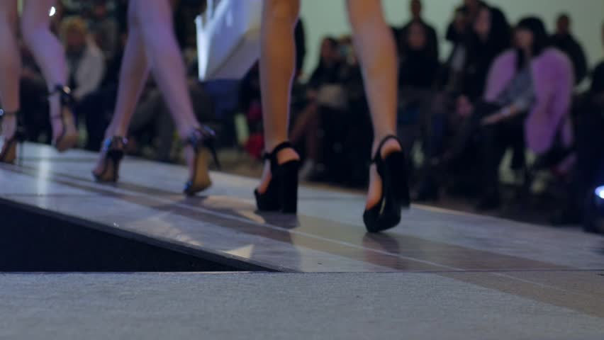 beautiful female legs in high heels during fashion show close-up