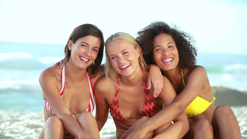 Three smiling girls embracing each other at the beach
