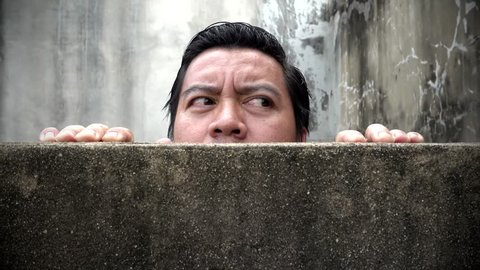 Asian men climb up concrete walls appearing suspiciously.