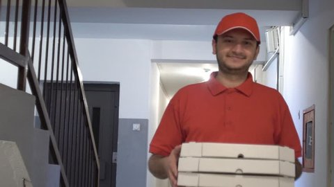 SLOW MOTION: Delivery boy in a red uniform holding a stack of pizza boxes making a home delivery. Stabilized tracking footage.