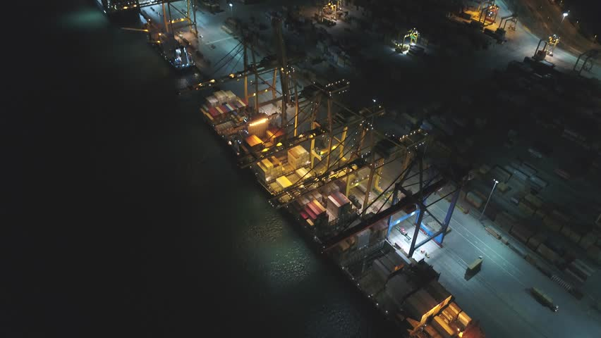 Aerial Steel cranes loading heavy cargo freight, container shipment  on large anchored freighter ships in seaport
