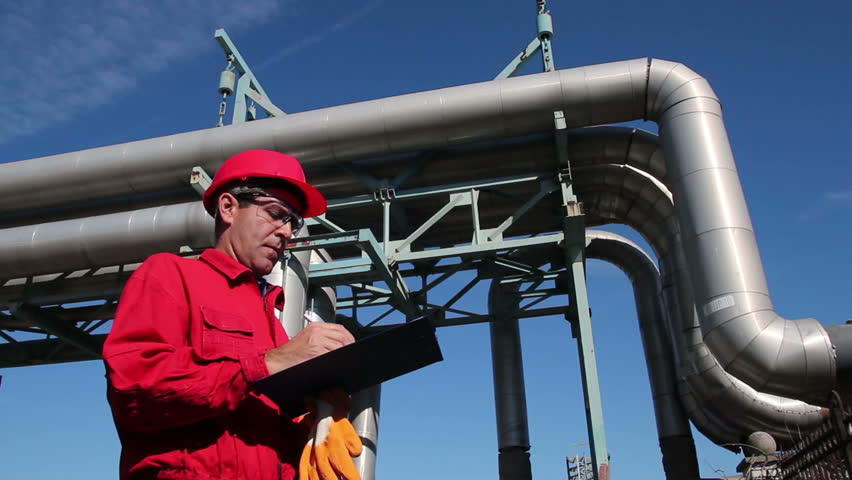 Refinery Worker and Pipelines. Worker wearing red overalls and hardhat , writing on clipboard next to pipelines. HD1080p.
