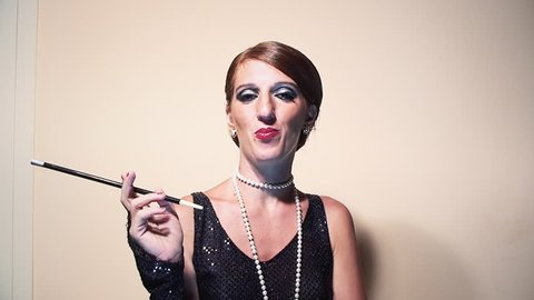 A silent cool lady wih a 1920s hairstyle and makeup, holding a cigarette holder. Medium shot.