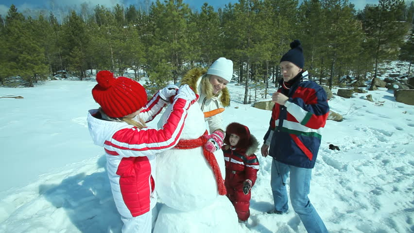 Cheerful family enjoying themselves on a winter day making a snowman