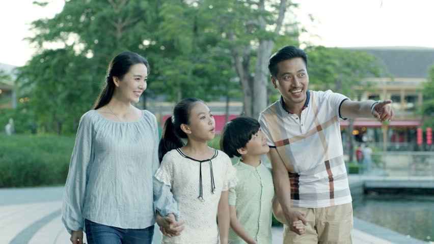 happy asian family of 4 pointing & walking toward camera in slow motion