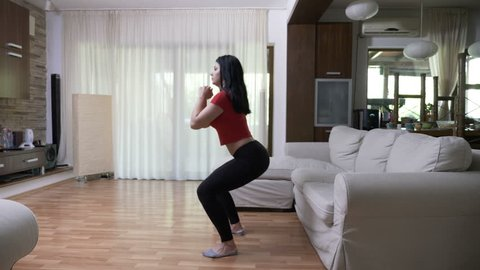 Young sexy attractive woman watching TV fitness tutorial exercising in the living room at home