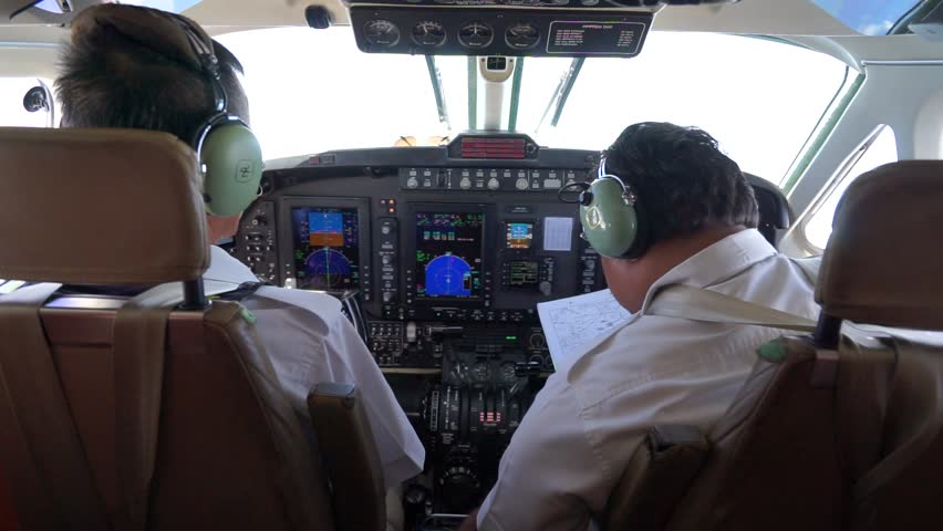 Seletar, Singapore - August 3,2017: Two pilots are discussing for their flight plan in the cockpit of Beechcraft Super King Air B200GT aircraft.