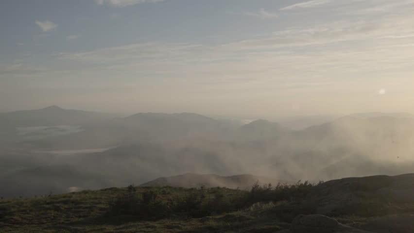 Fog rolls over majestic sunrise over Adirondack mountains.