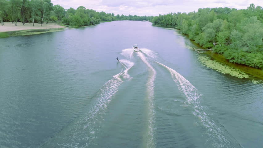 Flying over wakeboarding on river 4k aerial video. Wakeboarder surfing behind boat trails and doing tricks: somersault flip jump | Shutterstock HD Video #30176554
