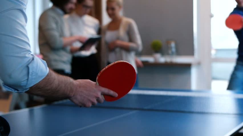 workers taking a break and playing ping pong in a creative start up work environment -