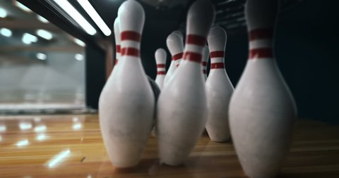 Bowling strike, bowling ball knocks down bowling pins in slow motion