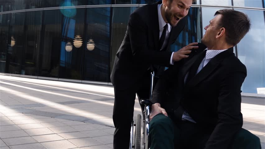 Happy disabled business man in wheelchair, spending time in business deal district with his friend, smiling and supporting handicapped male good mood and blow to the shoulder. Slow motion | Shutterstock HD Video #30221224
