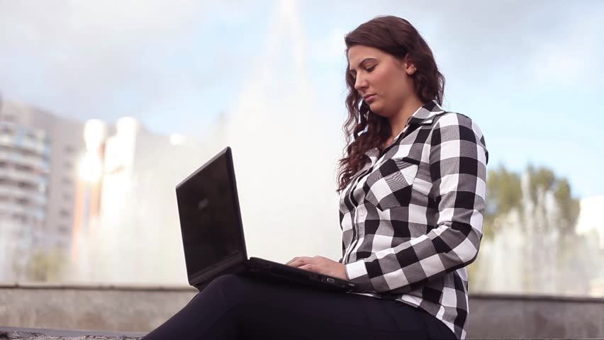Young beautiful happy girl resting while sitting by the fountain in the city with laptop | Shutterstock HD Video #30223231