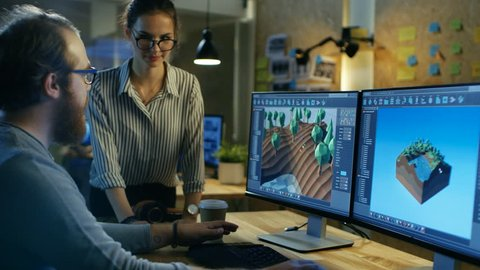 Male Game Developer Talks with Artistic Female Level Designer. Two Displays Show Totally Original Game. They Work in a Creative Office Loft. Shot on RED EPIC-W 8K Helium Cinema Camera.