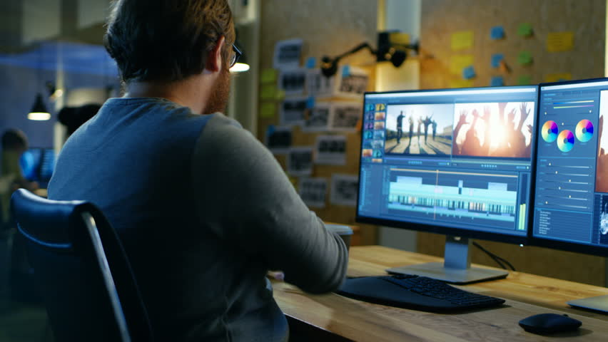Male Videographer Edits and Cuts Footage and Sound on His Personal Computer, Puts on His Monitors/ Headphones. His Office is Modern and Creative Loft Studio. Shot on RED EPIC-W 8K Helium Cinema Camera