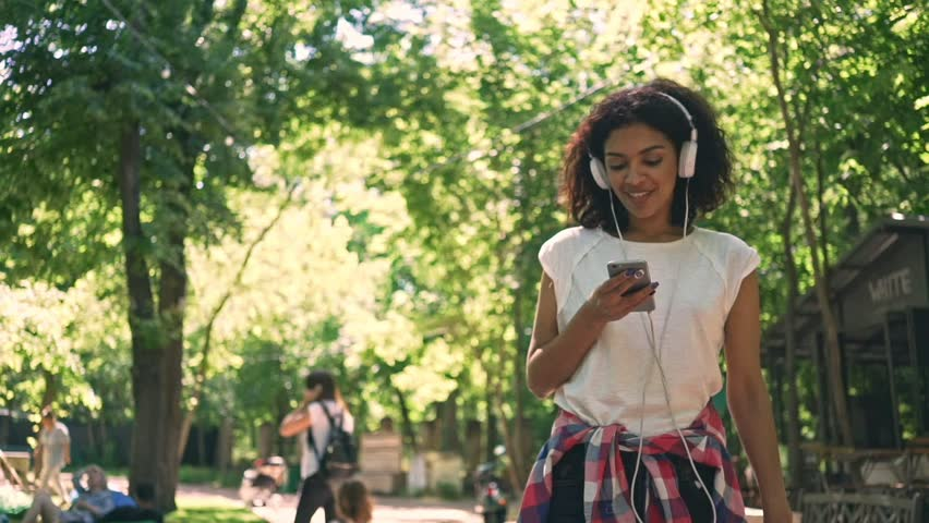 Smiling young african lady walking at the park outdoors chatting by phone listening music
