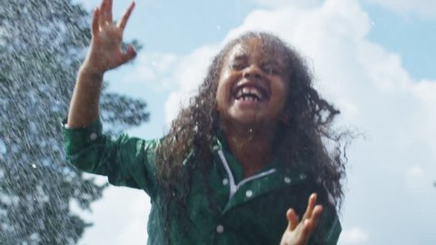 Tilt down of excited little African-American girl in green rubber boots and raincoat jumping in puddle in rain