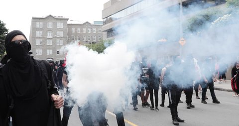 Quebec, Canada - August 2017 - A protester throws a smoke bomb during an anti-racism protest.
