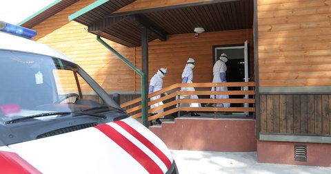 Three unrecognizable doctors or nurses wearing full Ebola virus protection uniform  come in home of patient. Ambulance car on background. Epidemic in the city. Evacuation and disinfection. 4K footage.