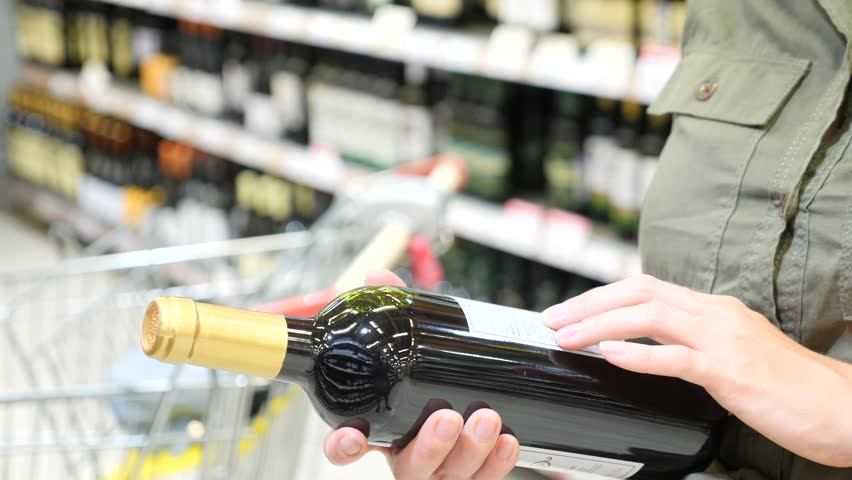 Man chooses alcoholic drinks on the counter of alcoholic department supermarket. 4k, slow-motion