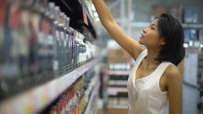 Young Thai Woman picking alcohol in hypermarket 4k UHD (3840x2160) | Shutterstock HD Video #30257434