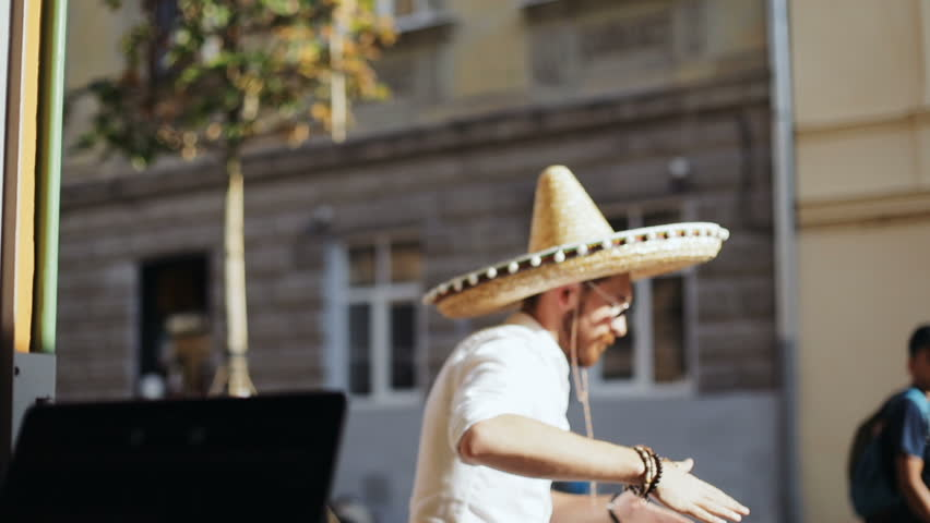 Mexican party concept - portrait of young attractive bearded man with glasses in casual wear with mexican sombrero dancing at the city urban old architecture street