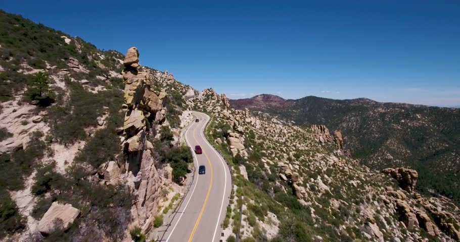 Cars driving down a curved Mt.Lemon road in Tucson AZ.