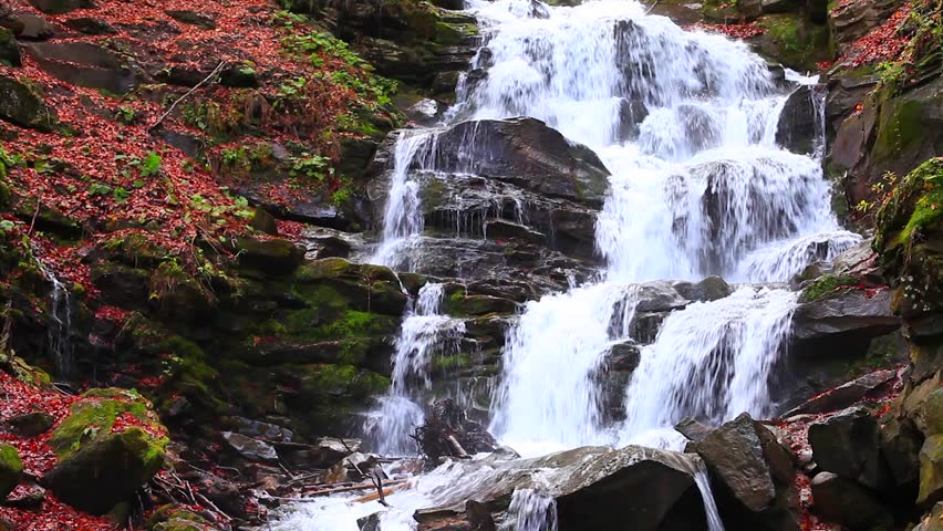 Waterfall in autumn forest. Vivid colors.