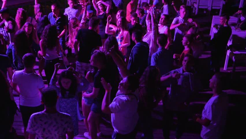 Skadovsk, Ukraine - 12 August 2017: Crowd Dancing at bright lighting in slow motion, disco party in Skadovsk, 12 August 2017. #30280474