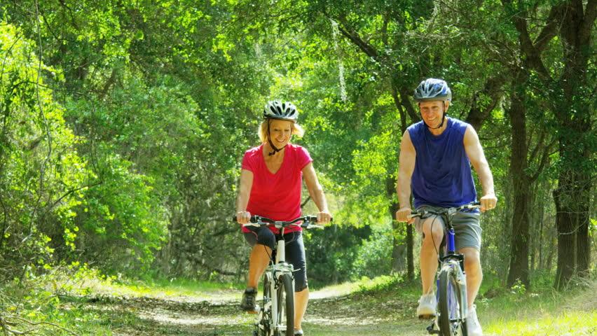 Retired Caucasian American couple having fun enjoying cycling outdoors RED WEAPON
